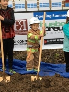 Collin Barrett, son of Fire Chief Jon Barrett, poses in uniform with his golden shovel at the groundbreaking ceremony of the Cicero Fire Department's future fire station.