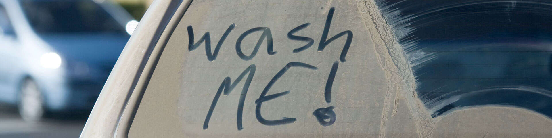 """Wash me"" phrase on a dirty car window"