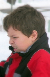 boy squinting with effort in snow