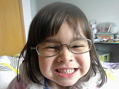 girl with glasses smiling at camera up close