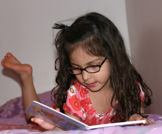 girl laying on stomach, reading a book