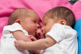 two newborn babies sleeping together