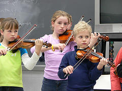 3 children practicing violin