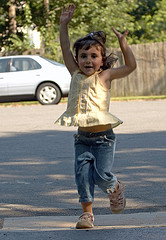 young girl finishing race, arms raised in triumph