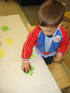 toddler boy playing at table in daycare