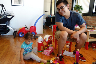 teen boy watching toddler girl play with toys