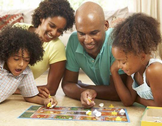 parents and 2 children playing board game