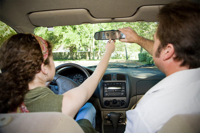 teen and parent adjusting rearview mirror of car