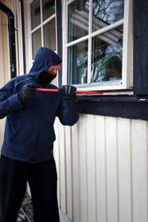 masked man breaking into a home
