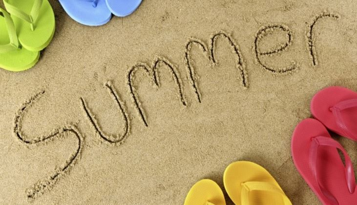 the word summer scratched into sand with flip flops nearby