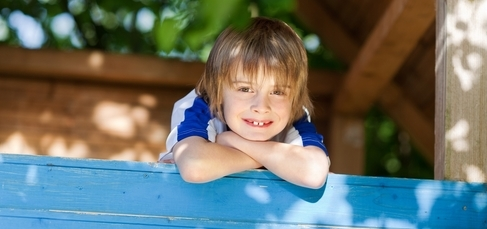 boy leaning head on arms, smiling while outdoors