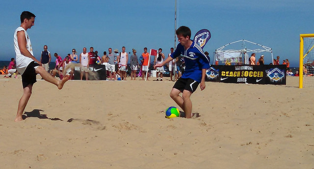 boy playing defensive soccer on the beach