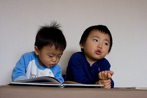 2 toddlers looking at book