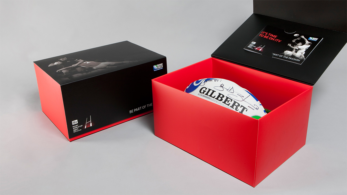 Image of the Rugby World Cup direct mail campaign with a signed rugby ball inside a box. Earnie creative design