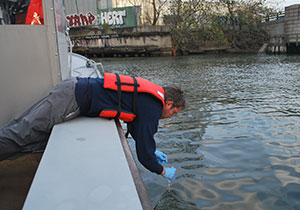 Persona tomando muestra de agua en el Rio Hudson