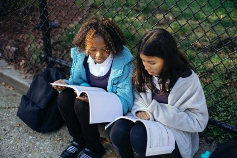 Two children doing homework next to a fence outside