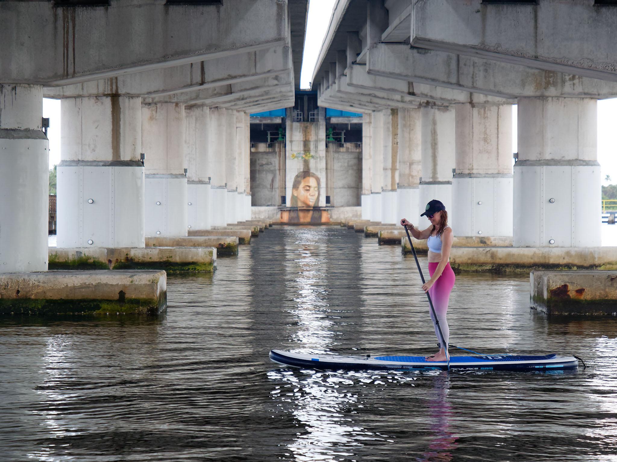 SUP paddling under a bridge