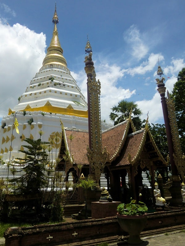 A Buddhist temple in Chiang Mai, Thailand, on a sunny day with blue skies.