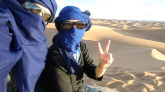 People shrouded in blue cloth give peace sign in the Sahara Desert