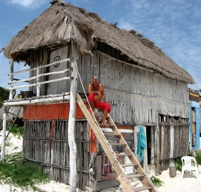 A man sits on the stairs to a beach hut in Tulum, Mexico