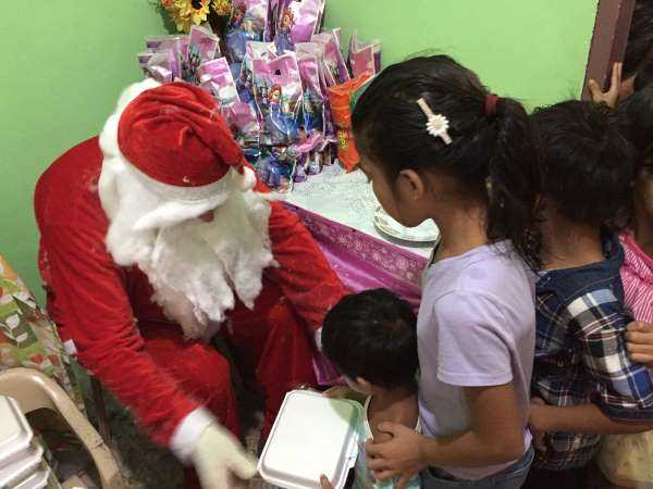 Santa hands a child a meal, as part of my cultural travel lesson at a Filipino Christmas party