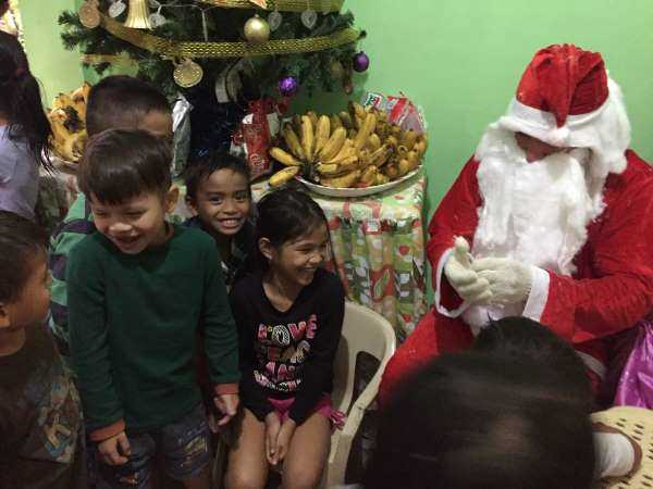 Santa and kids at a party in the Philippines illustrate a cultural travel lesson