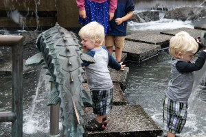 Twin boys playing at water fountain