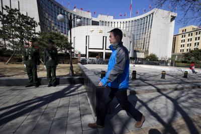 A Chinese man walks past Chinese paramilitary policemen on duty outside the Peoples Bank of China in Beijing on 13 March 2013. (Photo: AAP)