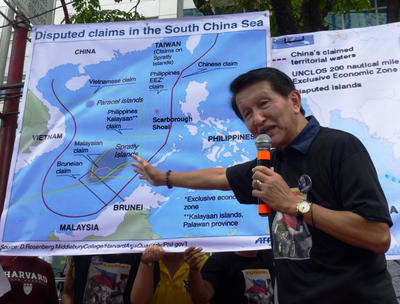 The Philippines former National Security Adviser Roilo Golez points to an image showing Chinese claims in the South China Sea during a rally on 24 July 2013 in Manila. (Photo: AAP)