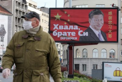 A man wearing a protective mask passes by a billboard depicting Chinese President Xi Jinping as the spread of the coronavirus disease (COVID-19) continues in Belgrade, Serbia, 1 April 2020. The text on the billboard reads 'Thanks, brother Xi' (Photo: Reuters/Djordje Kojadinovic).