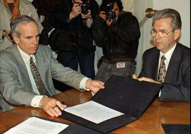 FILE - In this July 7, 1997, file photo, American millionaire Douglas Tompkins, left, and Juan Villarzu, chief of staff of the Chilean president, hold the text of an accord signed in Santiago, Chile. Officials in Chile said Tuesday, Dec. 8, 2015, that the wealthy U.S. businessman and environmental activist has died from severe hypothermia in a kayaking accident. (AP Photo/Santiago Llanquin, File)