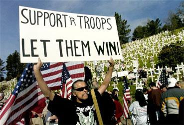 A man, who gave his name as Chief, who supports the U.S. war in Iraq, holds a sign in support of U.S. troops during a rally, Thursday, March 8, 2007, in Lafayette, Calif. Demonstrators in support of the war in Iraq gathered beneath a hillside where anti-war activists have planted hundreds of crosses to represent soldiers killed in Iraq. The caravan of demonstrators, which began Thursday, in San Francisco, is heading across the country to Washington, D.C. (AP Photo/Noah Berger)