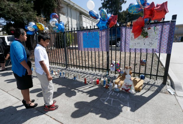 People visit a memorial for accident victim Jeremiah Esera, 2, at 35th and Penniman Avenues in Oakland, Calif., on Wednesday, Sept. 21, 2016. The boy was hit and killed by an AC Transit bus on Tuesday when he ran into the street, police said. (Jane Tyska/Bay Area News Group)