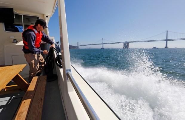 Master deckhand Matthew Cosby wraps up a line as the Heron, Tideland Marine Group's 52-foot Chesapeake yacht, cuts through the waters of the San Francisco Bay in San Francisco, Calif., on Wednesday, Sept. 28, 2016. Tideline Marine Group is breaking into the public commuter service with a ferry run between Berkeley and San Francisco and other commuter service ventures. (Laura A. Oda/Bay Area News Group)