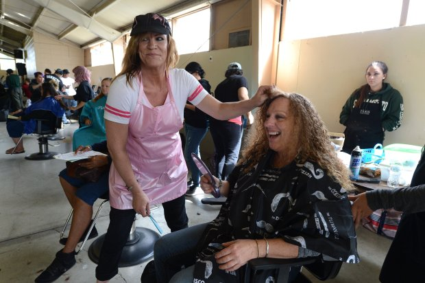 Barbara Jones spots a friend as she gets her hair cut by Sheila Gustafson, of the Paris Beauty College in Concord, at the Contra Costa Health Services' Project Homeless Connect at the Contra Costa County Fairgrounds in Antioch, Calif., on Thursday, Oct. 13, 2016. This was a one-day, one-stop event for the homeless that provided social and medical services as well as other types of assistance. (Dan Honda/Bay Area News Group)