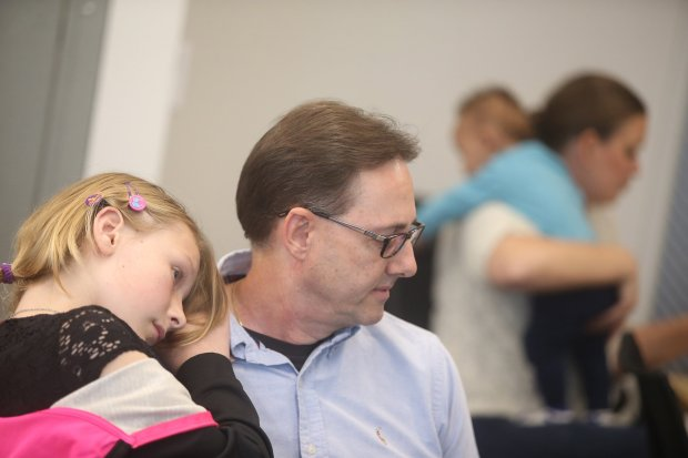 Taylor Kahn ,10, left, rests her head on her father Mark Kahn's shoulder during a adoption celebration event at the Alameda County Social Services Agency on Wednesday, Nov. 16, 2016, in Oakland, Calif. (Aric Crabb/Bay Area News Group)