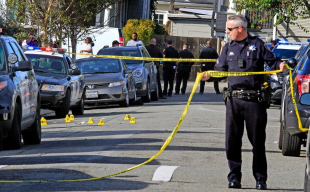 Oakland police put up yellow tape at the scene of a double homicide on the 700 block of 39th Street in Oakland on Monday as friends and family begin to gather in mourning. (Laura A. Oda/Bay Area News Group)