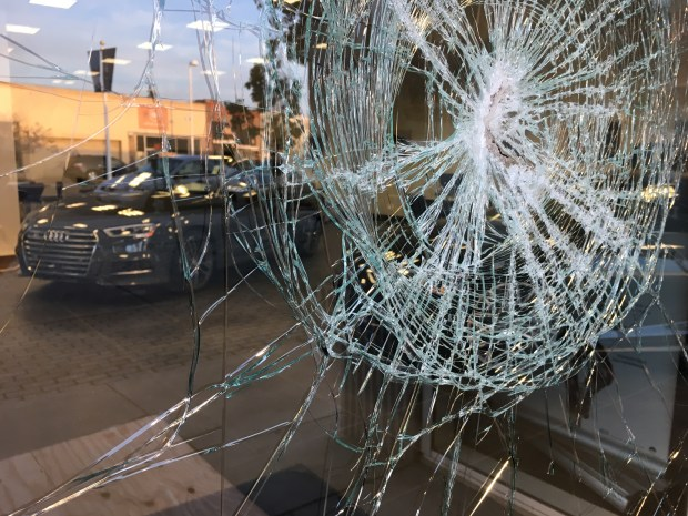 The front door of the Audi dealership on Webster Street in Oakland Calif. is shattered along with three large windows and a car, on Friday, Nov. 11, 2016, after another protest marched through Oakland Thursday night. (Laura A. Oda/Bay Area News Group)