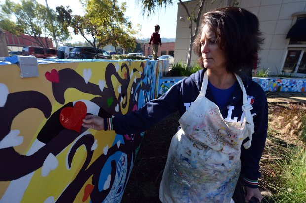 """Colleen Gianatiempo checks the placement of a ceramic heart as she works on her mural """"Small Town, Big Heart"""" in downtown Martinez, Calif., on Friday, Nov. 18, 2016. (Kristopher Skinner/Bay Area News Group)"""
