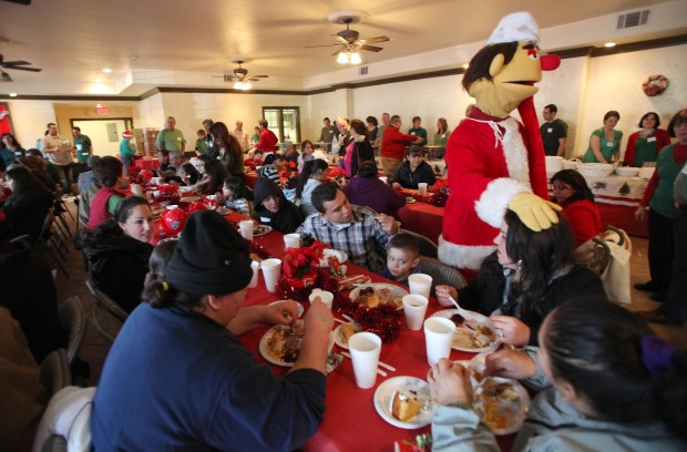 "Volunteer Martk Pitzlim, of Martinez, dressed as ""Mr. Q.,"" right, greets diners during the Christmas for Everyone meal at the New Hope International Church in Concord, Calif. on Sunday, Dec. 25, 2011. 3,000 people were expected for the event which also featured free presents, haircuts, clothing distribution, games and live entertainment. (Jane Tyska/Staff)"