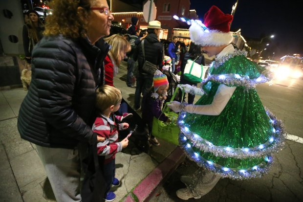 A member of the Tap Dancing Christmas Trees hands out candy during the Montclair Holiday Stroll on Dec. 1, 2016.(Aric Crabb/Staff archives)