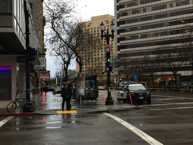 Oakland police stand by a taped-off section of the 1300 block of Broadway after a reported shooting hit at least one person Tuesday, Jan. 10, 2017.