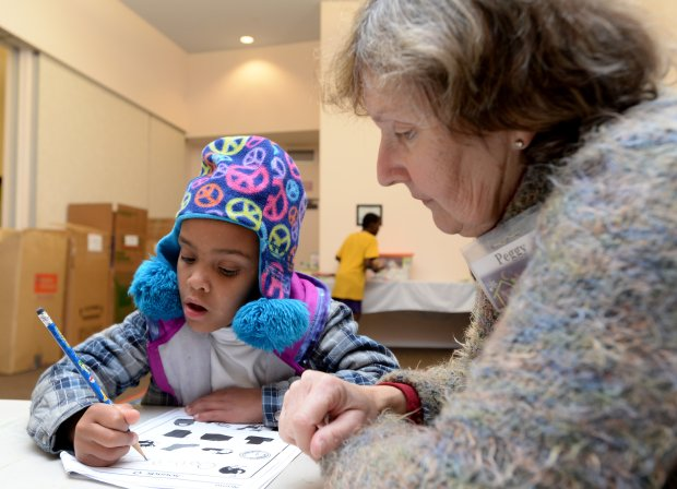 Before dinner, Amara Taylor, 5, from the Pittsburg Antioch area works on her homework with volunteer tutor Peggy Woehleke, of Moraga, at the Warm Winter Nights shelter set up at St. John Vianney Catholic Church in Walnut Creek, Calif., on Tuesday, Jan.17, 2017. Warm Winter Nights is a rotating family shelter set up during the winter months through the Social Justice Alliance and the Interfaith Council of Contra Costa County. Woehleke also works with the students in a reading program where they can earn free movie tickets by reading. (Susan Tripp Pollard/Bay Area News Group)