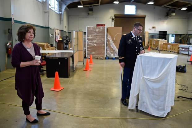 """Trinity Center director Donna Colombo stands as she listens to National Guard Lt. Col. Bryan Keels speak during the Trinity Center's """"Winter Nights Shelter"""" program at the National Guard armory building in Walnut Creek, Calif. on Thursday, March 30, 2017. Tonight ends the 5-month long program that allowed homeless people to sleep at the armory. Trinity Center held a dinner tonight thanking everyone who helped get the program started with the hope of continuing the program next year. (Jose Carlos Fajardo/Bay Area News Group)"""