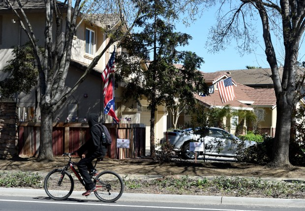 A young man rides by along Garin Parkway near the home of Eric Harvey, who displays American and confederate flags in front of his home on Craig Court in Brentwood, Calif., on Monday, March 13, 2017. The side of his home is along side Garin Parkway, a popular thoroughfare, where some motorist have voiced their opinions objecting and supporting Harvey's flags. Harvey drew his neighbor's ire when he began flying the confederate flag last week. (Susan Tripp Pollard/Bay Area News Group)