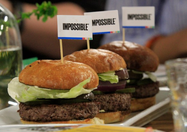 """Three """"impossible Burgers"""" are served after a panel discussion about the plant-based meat during an event announcing the new facility under construction for Impossible Foods in Oakland, Calif., on Wednesday, March 22, 2017. (Laura A. Oda/Bay Area News Group)"""