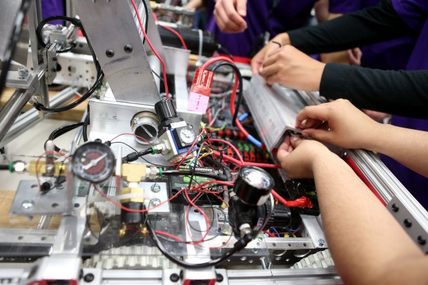 Members of team E.W.A. (Engineers With Attitude) make adjustments to their robot in the pit area between matches at the FIRST (For Inspiration and Recognition of Science and Technology) robotics competition held at St. Ignatius College Preparatory in San Francisco, Calif., on Saturday, March 18, 2017. Some 40 high school teams competed in the robotics competition that builds science, engineering, and technology skills. (Anda Chu/Bay Area News Group)