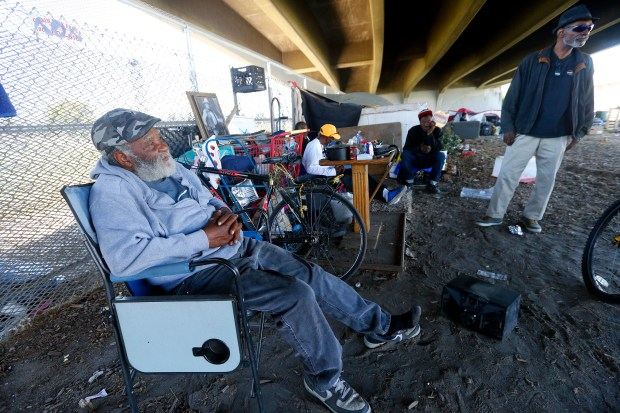 Clarence Wheeler, 77, left, is photographed at a homeless camp along E 12th Street on Tuesday, May 2, 2017, in Oakland, Calif. A fire tore through the camp two weeks ago killing a dog and destroying property at the camp. (Aric Crabb/Bay Area News Group)