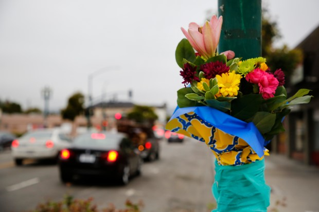 Flowers were left at the scene of a fatal crash on the corner of Webb Avenue and Park Street in Alameda, Calif., on Tuesday, May 30, 2017. A truck carrying seven passengers rolled after a collision with a minivan, landing in front of Alameda Bicycle. Two people died and five others in the truck were injured. (Laura A. Oda/Bay Area News Group)