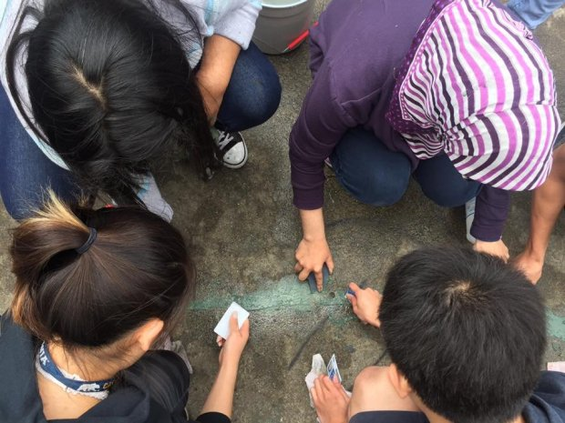 Some Irvington High School seniors vandalized the school's property andspray-painted a swastika late Sunday night as part of a senior prank, officials said. In this photo, some seniors work to scrape some of the swastika paint off the courtyard pavement. (Photo credit: The Irvington Voice Facebook page)